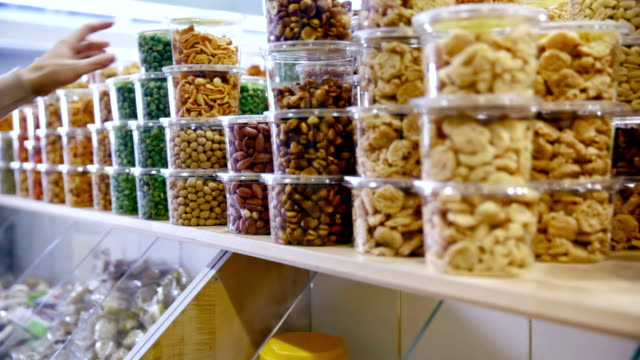 customer purchases dried fruits and nuts in grocery - nuts 個影片檔及 b 捲影像