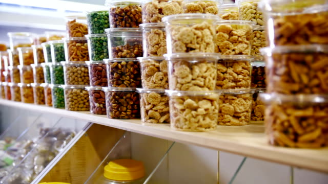Customer purchases shelled pistachios and nuts in grocery Customer purchases jar of shelled pistachios and nuts in grocery snack stock videos & royalty-free footage