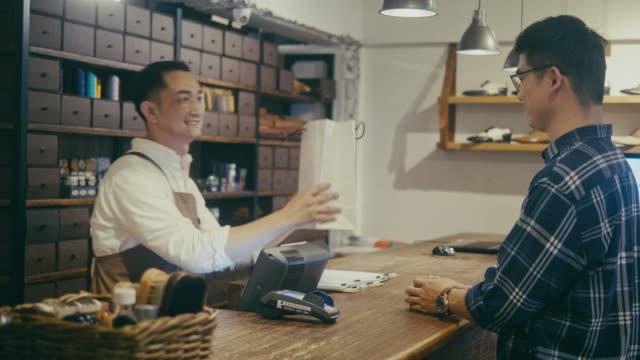 vídeos de stock, filmes e b-roll de cliente que recebe seu produto após o pagamento na loja de sapata dos homens (movimento lento) - boutique