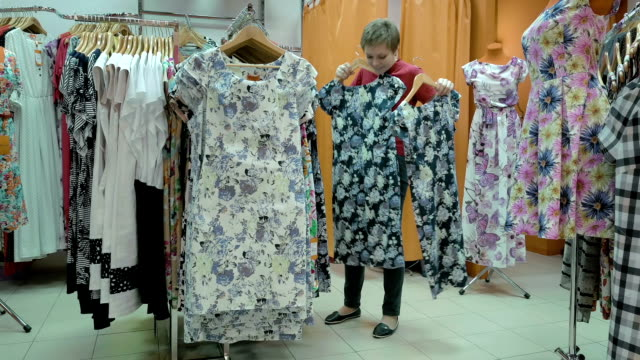 A customer searches the best suitable size for her A customer is in the process of finding the best suitable size for her. Dresses are available in various size, print and fabric. household fixture stock videos & royalty-free footage