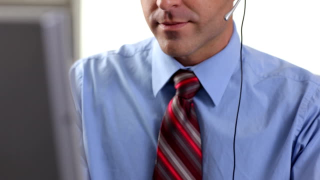 Customer service person talking on headset in office video
