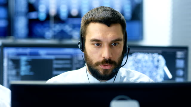 customer service representative answer client's questions in a headset. he works for a big technological company. office has multi-ethnic team of specialists, displays show useful information. - обслуживание стоковые видео и кадры b-roll