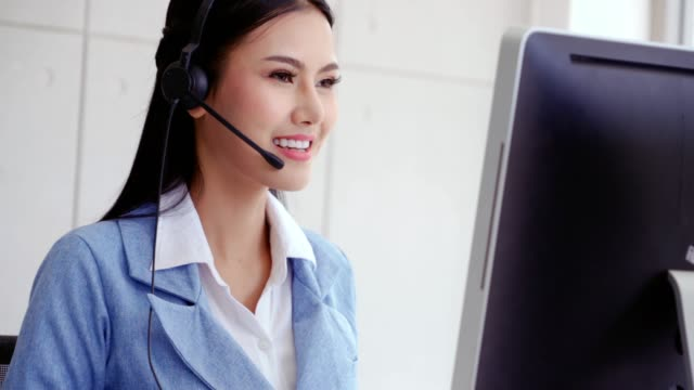 Customer support agent or call center with headset talking to customer on phone. Customer support agent or call center with headset works on desktop computer while supporting the customer on phone call. Operator service business representative concept. call center stock videos & royalty-free footage