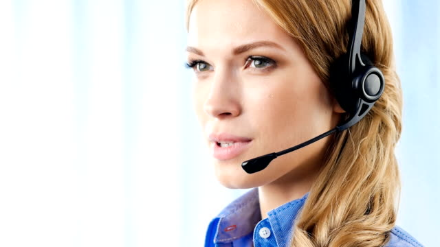 Customer support operator smiling, speaking, looking at camera, in office video