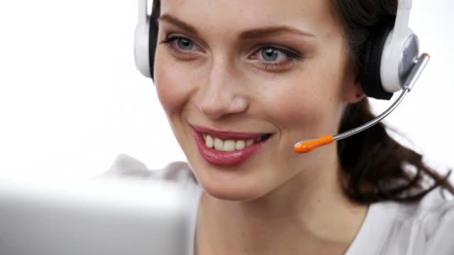 Operador de soporte al cliente sonriendo y hablando y mirando a la cámara, sobre blanco - vídeo