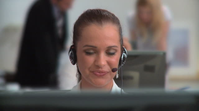 HD DOLLY: Customer Support HD1080p: DOLLY shot of a young woman sitting behind a desk in the customer support center and talking over the headset,  in the blurred background other office workers are sitting and working. call centre videos stock videos & royalty-free footage