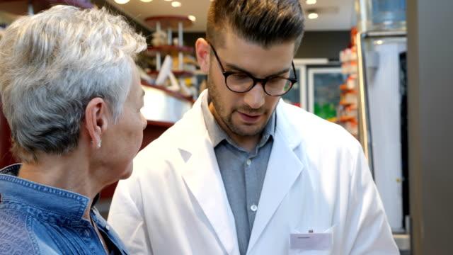 kunden im gespräch mit chemiker über medizin im store - kosmetik beratung stock-videos und b-roll-filmmaterial