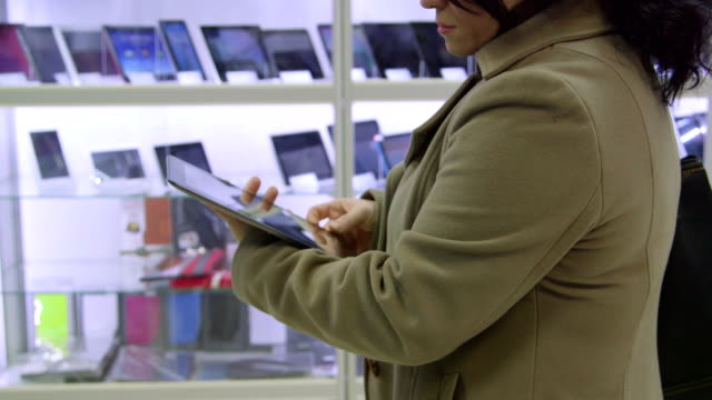 Customer testing new digital tablet at electronics store video