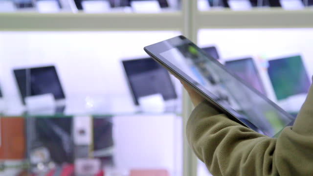 DOLLY: Customer testing new digital tablet at electronics store