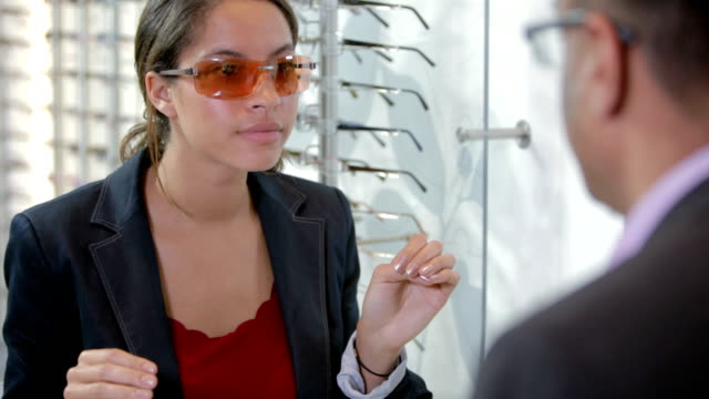 Customer tries on sunglasses at an optician video