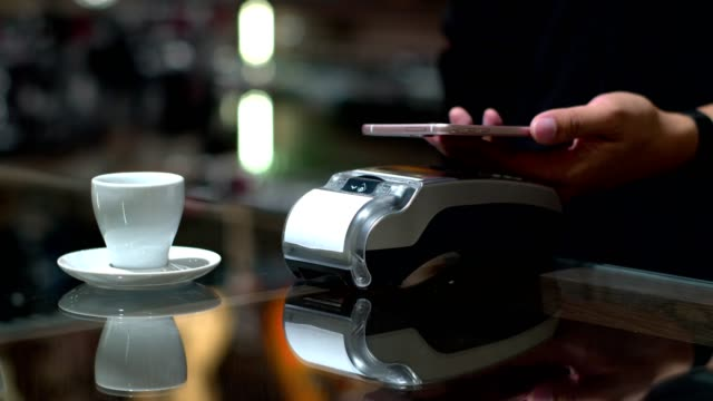 Customer using mobile payment coffee with credit transaction in cafe