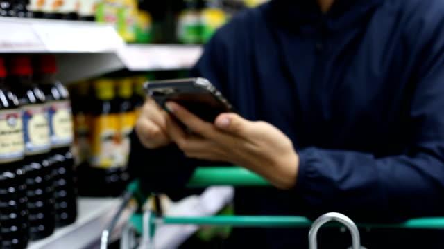 kund som använder smart telefon i supermarket - dagligvaruhandel, hylla, bakgrund, blurred bildbanksvideor och videomaterial från bakom kulisserna