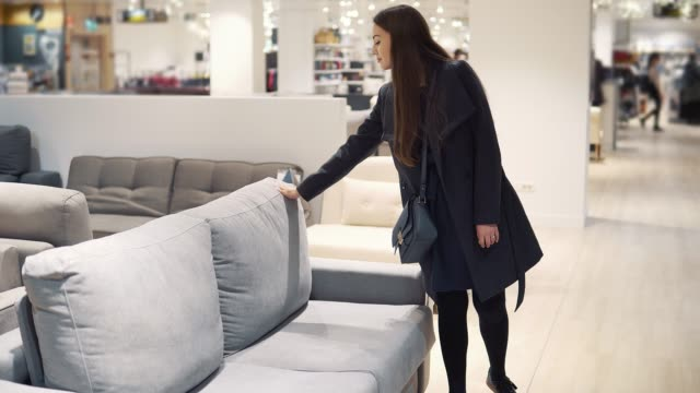 Customer woman buying new furniture - sofa or couch in a store video