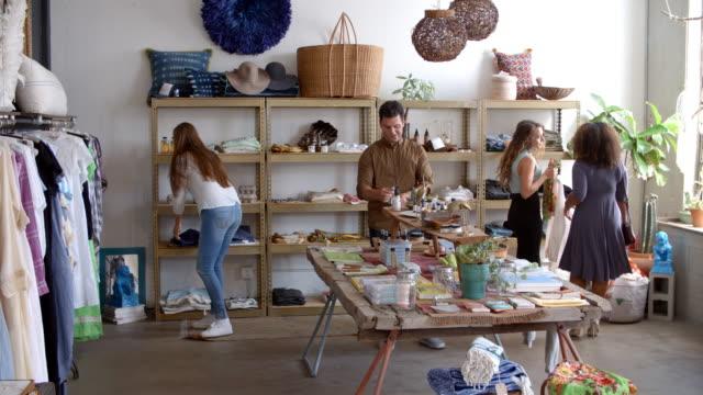 vídeos de stock, filmes e b-roll de assistente de vendas e clientes em uma loja de roupas ocupado - boutique