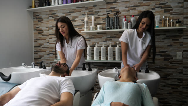 Customers at the hair salon getting their a shampoo looking relaxed Customers at the hair salon getting their a shampoo looking relaxed and happy beauty salon stock videos & royalty-free footage