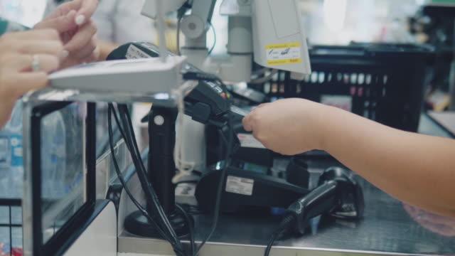 клиенты покупают продукты питания и продукты питания в кассе и платят в кассе. супермаркет магазин. - касса стоковые видео и кадры b-roll
