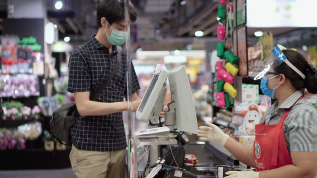 vídeos de stock e filmes b-roll de customers buying food and staples from a cashier and paying at the till. supermarket - supermarket worker