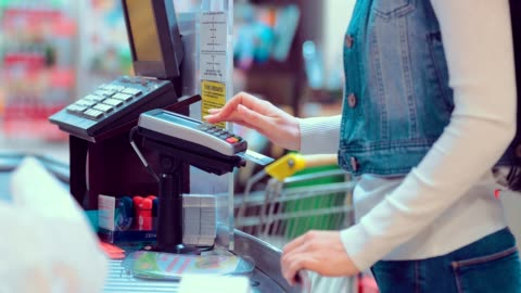 vídeos de stock e filmes b-roll de customers buying food and staples from a cashier and paying at the till. supermarket store. close-up - consumismo