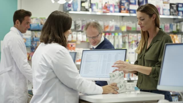 Customers buying medicines from chemist at store Slow motion shot of woman buying medicines from female chemist. Male pharmacist is assisting to mature customer. They are at checkout counter in pharmacy. pharmacist stock videos & royalty-free footage