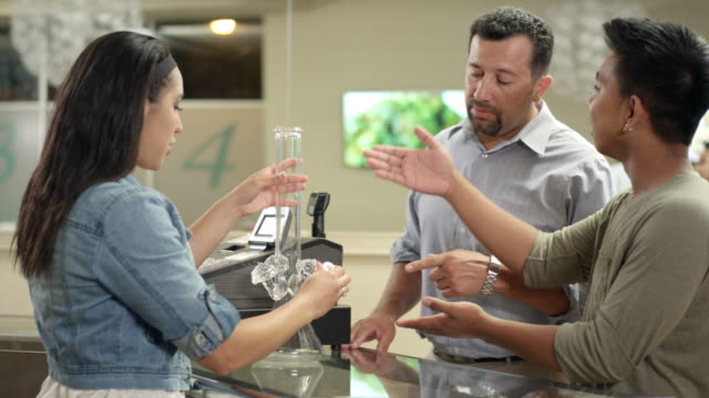 Customers checking out a large bong at a recreational marijuana shop video