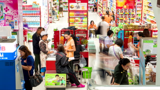 Customers paying for goods at the check counter in supermarket.