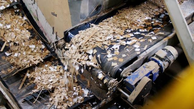 cut brown cardboard transported by conveyor in workshop pile of cut brown cardboard transported by black conveyor belt in papermaking plant lit workshop recycling stock videos & royalty-free footage