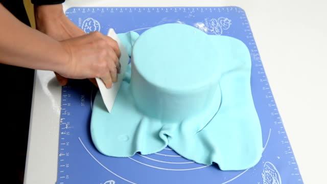 cut fondant after cover a cake - decorazione per dolci video stock e b–roll