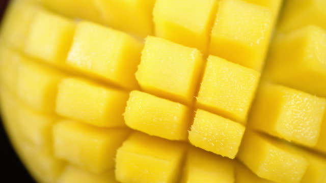 Cut into cubes mango slowly rotates. Cut into cubes mango slowly rotates. Macro background. The texture of the mango. mango stock videos & royalty-free footage
