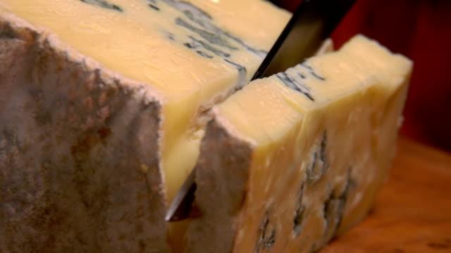 schneidstück käse mit blauen schimmelpilzen auf einem brett - scheibe portion stock-videos und b-roll-filmmaterial