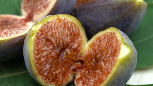 Cut ripe fig fruits cut in pieces on green leaves. Sweet and delicious food for healthy nutrition. Fig seeds full of vitamins and antioxidant effect
