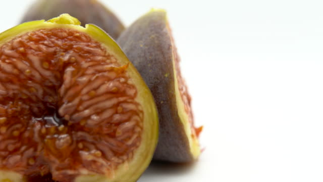 Cut ripe pieces of fresh figs isolated and rotating on white background. Sweet fruit with seeds inside, juicy exotic figs in shape of heart. Nutrition and healthy eating