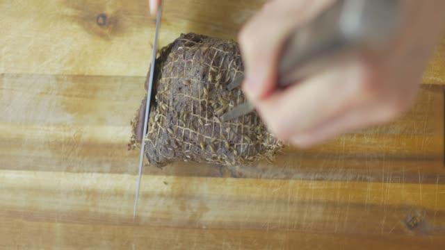 cut roasted beef on wooden chopping board
