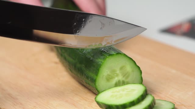 Cut the cucumber. A man with his hands cuts a cucumber with a knife on a wooden cutting Board. ingredient for salad