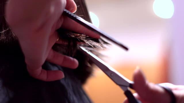 女性の髪をハサミで切ってください。 ビデオ