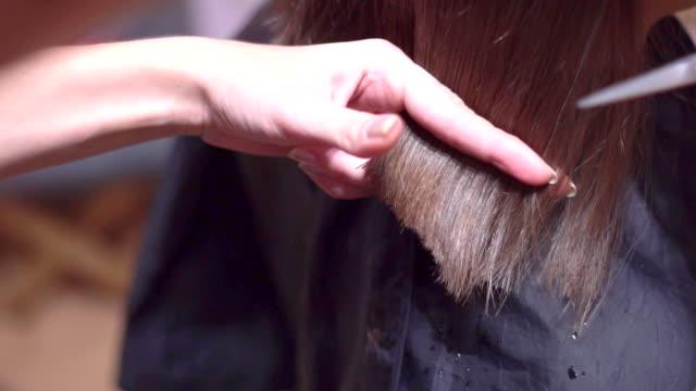 女性の髪をハサミで切ってください。 - 美容院点の映像素材/bロール