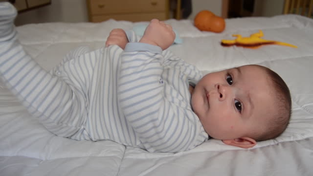 vídeos de stock e filmes b-roll de cute 4 months old baby boy lying on his back on the bed and stretching. - mês