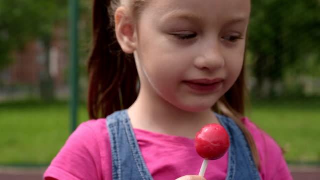 可愛的5歲女孩與棒糖 - 波板糖 個影片檔及 b 捲影像