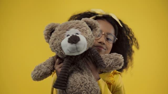 vídeos de stock e filmes b-roll de cute african american kid with teddy bear isolated on yellow - teddy bear