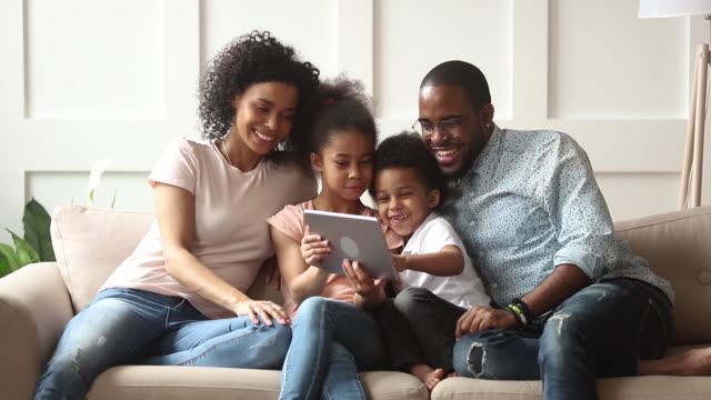 söt afrikanska barn spela spel med digital tablet med föräldrar - parent talking to child bildbanksvideor och videomaterial från bakom kulisserna