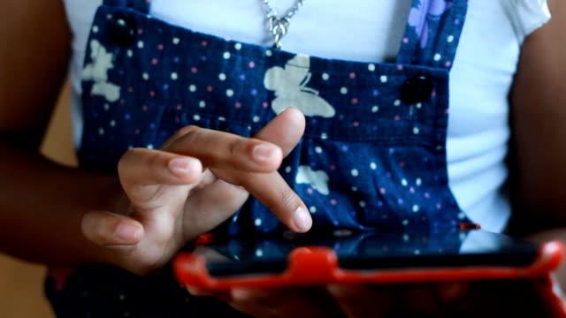 Cute African girl play tablet in coffee shop video