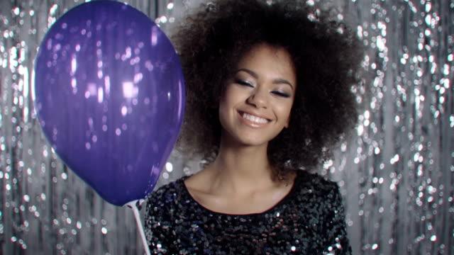 Linda mujer afro americano con globo soplando confeti sobre fondo brillante. - vídeo