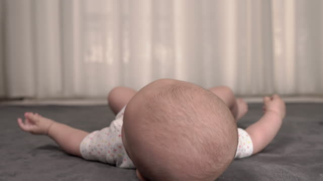 cute and active little baby boy lying and turning on the floor. kid studying new world. touching moments - rotolo video stock e b–roll