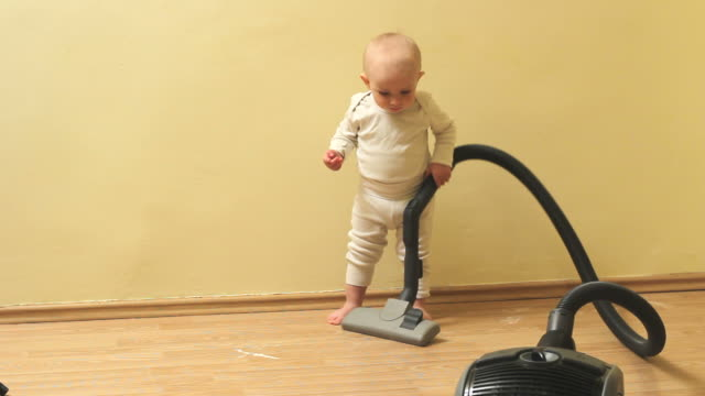 cute and diligent baby boy clean the house with vacuum cleaner - addetto alle pulizie video stock e b–roll