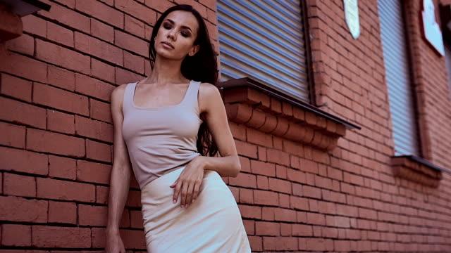 レンガの壁、ポージングのドレスでキュートでゴージャスなラテン系女性 ビデオ