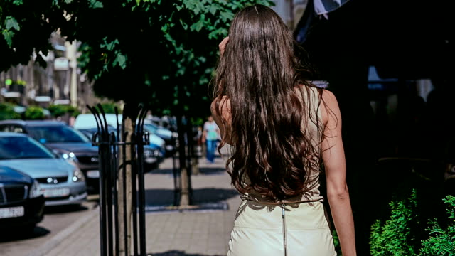 cute and gorgeous latin women in dress walks along the shady alley - city walking background video stock e b–roll