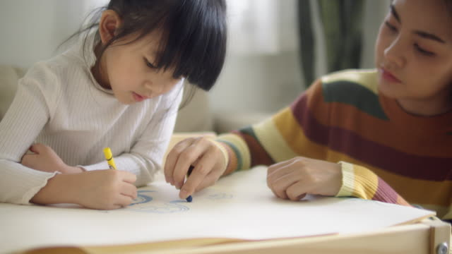 cute and lovely asian girl doing homework at home, with a help of her mother. - two students together asian video stock e b–roll