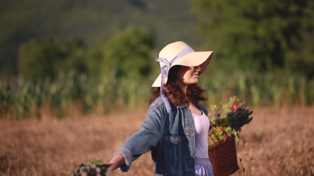 Cute and lovely girl with a basket full of flowers Lovely and gorgeous hipster girl in denim jacket, with a basket full of flowers and a hat, traveling through a golden wheat field. 天の川 stock videos & royalty-free footage