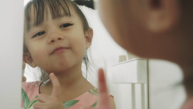cute asian baby girl is looking at mirror - solo una bambina femmina video stock e b–roll