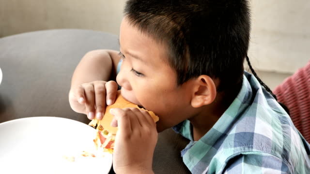 Cute asian boy are happy eating a hamburger in restaurant. Video 4k Slow motion