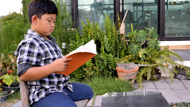 Cute asian children reading a book at home. education concept